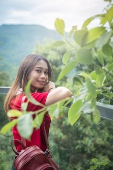 Turista de mulher asiática com passarela de ferro mochila vermelha