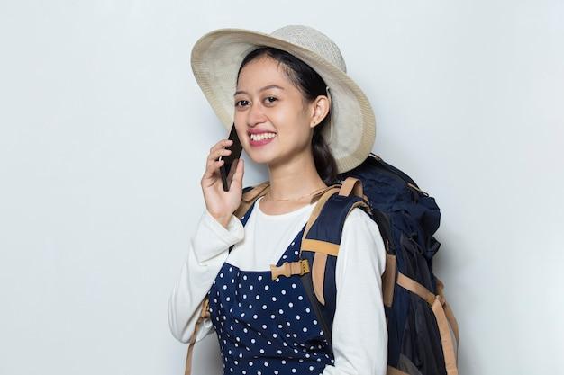 Turista de mulher asiática falando ao telefone, isolado no fundo branco