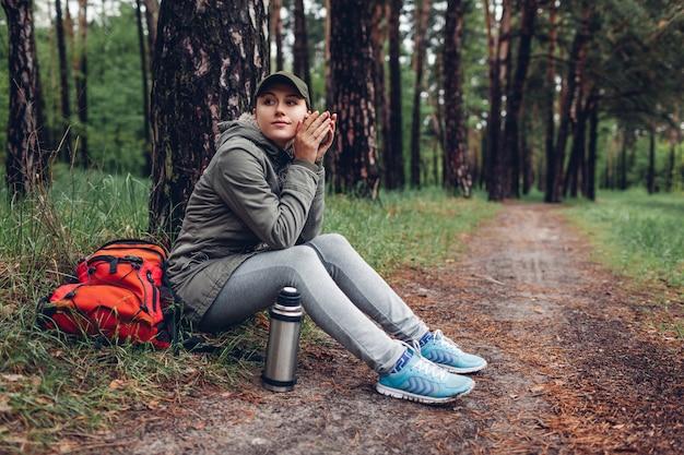 Turista de mulher bebe chá quente da xícara de garrafa térmica relaxante na floresta de primavera com mochila. camping, viagens e esporte