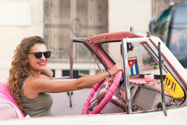 Turista de mulher bonita curtindo as férias de férias em cuba, dirigindo um carro clássico.