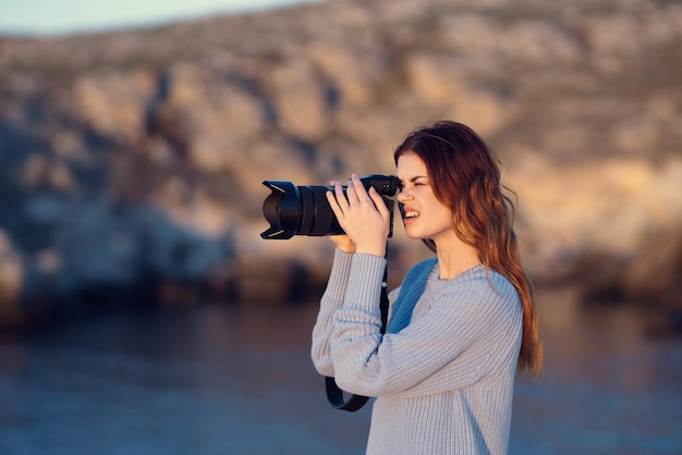 Turista de mulher com câmera na natureza montanhas rochosas viajam profissionais. foto de alta qualidade