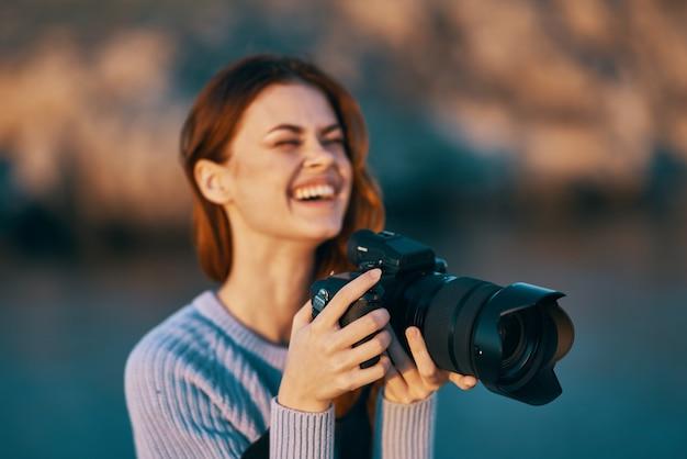 Turista de mulher com câmera na natureza profissional de viagens. foto de alta qualidade