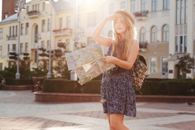 Turista de mulher com mapa na rua aponta o showplace