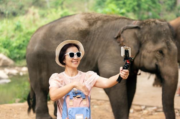 Turista de mulher de meia idade asiática relaxando e tirar uma foto com elefantes em chiang mai, tailândia.