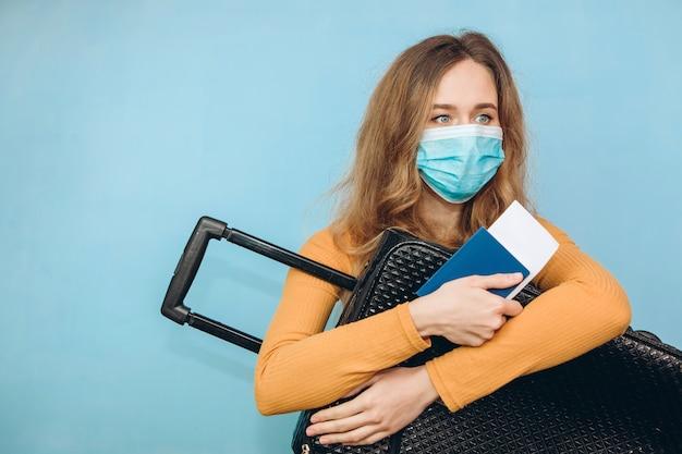 Turista de mulher em uma máscara médica senta-se com a bagagem nas mãos dele. surto de coronavírus covid-19. conceito de viagens e coroa. um turista não pode sair devido a uma pandemia.