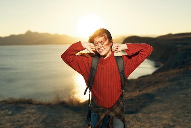 Turista de mulher emocional com as mãos levantadas no horizonte da natureza, pôr do sol