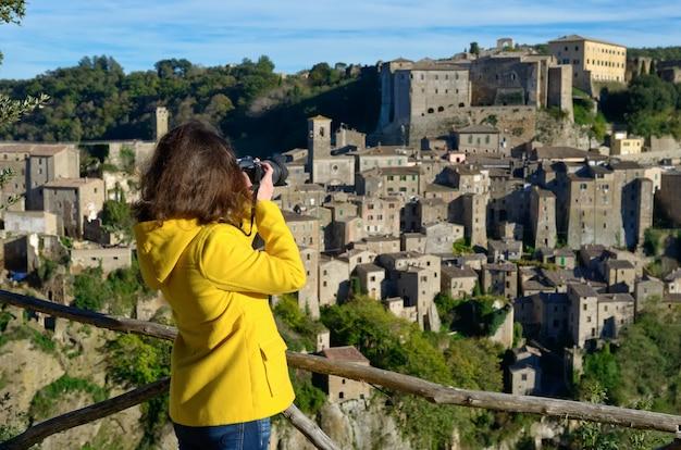 Turista de mulher fazendo foto da cidade medieval de sorano tuff na itália