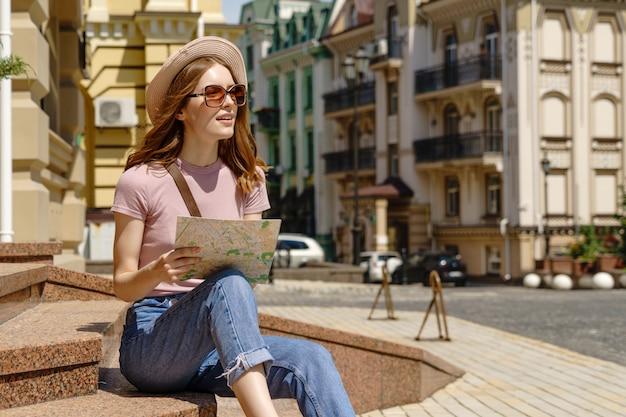 Turista de mulher jovem e bonita agradável com mapa da cidade, sentado nas escadas no centro da cidade.
