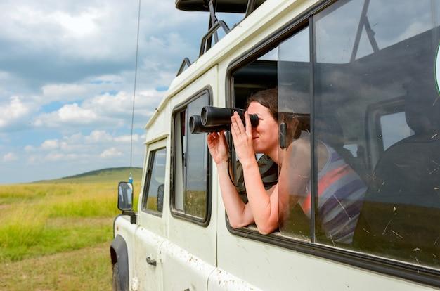 Turista de mulher no safari na áfrica, viajar no quênia, assistindo a vida selvagem na savana com binóculos
