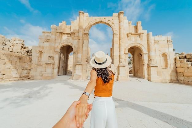 Turista de mulher no vestido de cor e chapéu, levando o homem ao portão sul da antiga cidade romana de gerasa