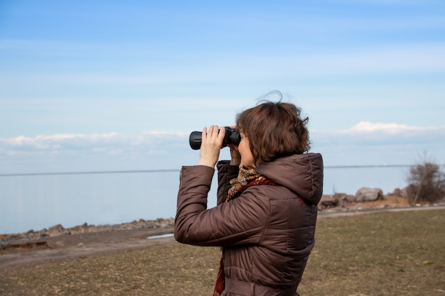 Turista de mulher olhando através de binóculos no mar distante, apreciando a paisagem. tempo outonal. mulher solitária no casaco marrom, olhando para o horizonte, céu azul. copie o espaço