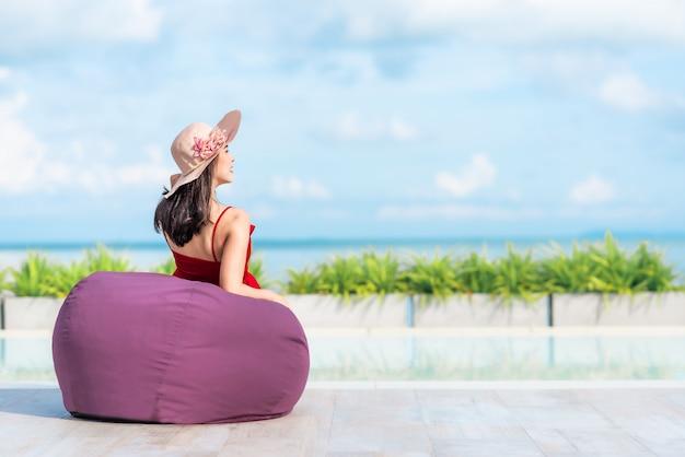 Turista de mulher relaxante no saco de feijão à beira da piscina no hotel