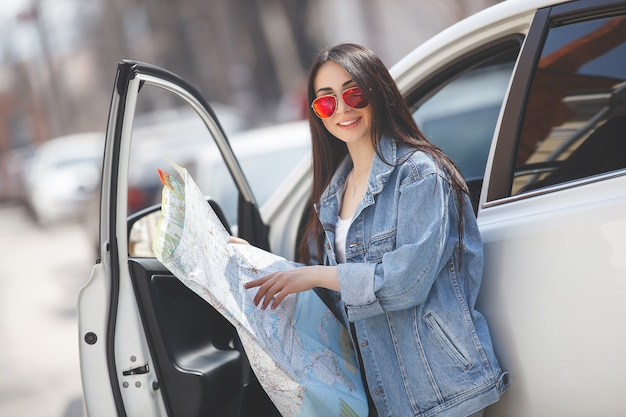 Turista de mulher segurando um mapa da cidade. viajante de carro navegando no país desconhecido. menina dirigindo um carro.