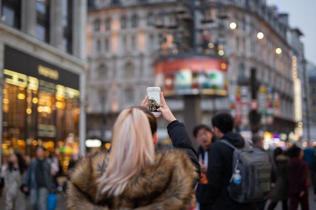 Turista de mulher tirando fotos da cidade com o celular na rua