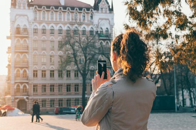 Turista de mulher tirando fotos de uma cidade velha ao pôr do sol