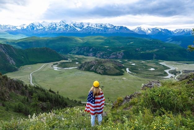 Turista de mulher traseira com bandeira americana olha para as montanhas. o conceito de viagem e aventura.
