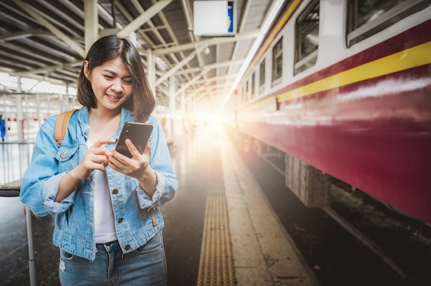 Turista de mulher usando smartphone na plataforma da estação de trem