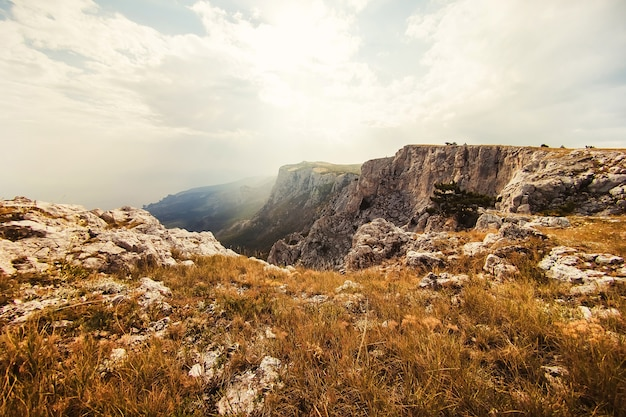 Turista de pernas contra o pano de fundo das montanhas. paisagem de montanha ao sol. montanhas poderosas. vista das montanhas para o mar.