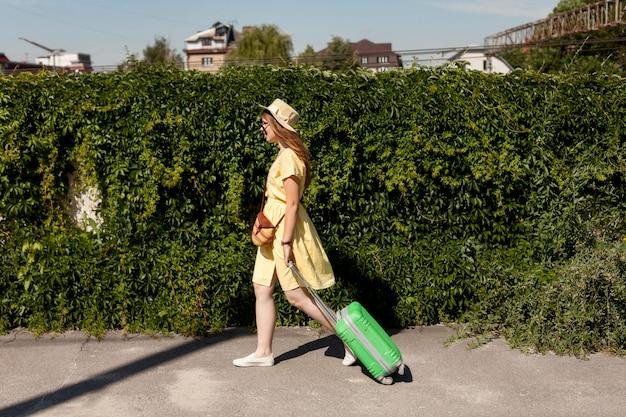 Turista de tiro completo andando com bagagem