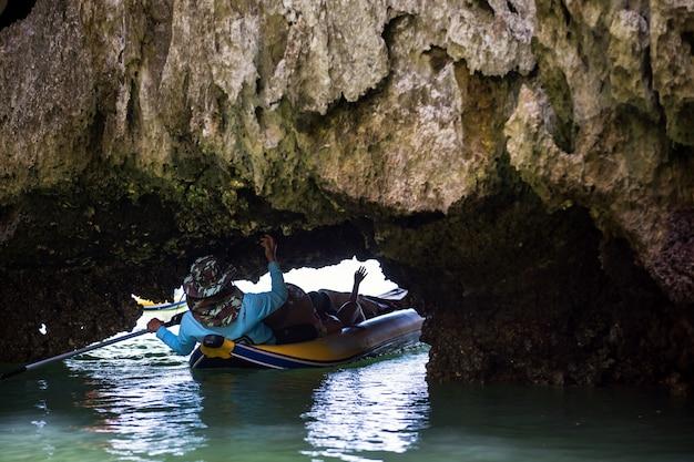 Turista deitado através da pequena caverna, phang nga