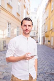Turista do homem com o telemóvel na rua de europa. caucasiano, menino, olhando câmera, ao ar livre