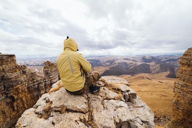 Turista do sexo masculino sentado no fundo de montanhas