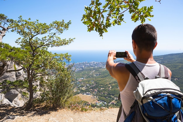 Turista do sexo masculino tira fotos em um smartphone da bela vista do mar em uma área montanhosa do topo entre as árvores coníferas. comunicação de vídeo, usando o telefone em viagens. cartão sim em roaming