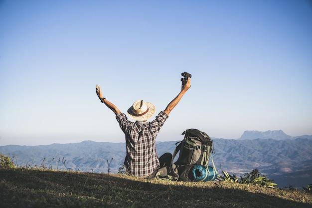 Turista do topo da montanha. raios solares. homem usar mochila grande contra a luz do sol
