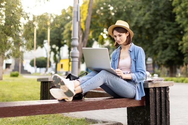 Turista elegante com chapéu, verificando o laptop ao ar livre