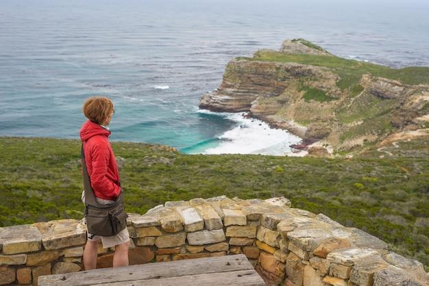 Turista em cape point, olhando a vista do cabo da boa esperança e praia dias