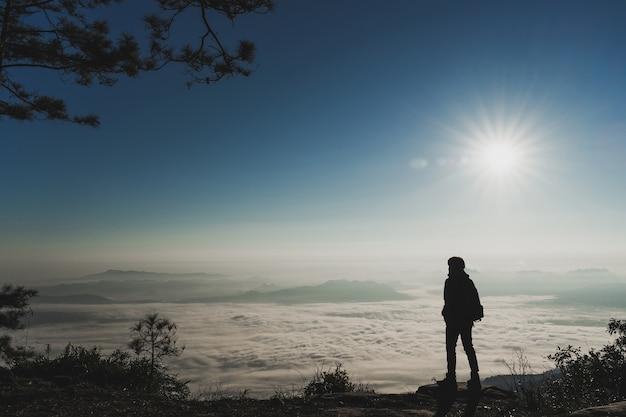 Turista em pé e apreciar a vista no topo das montanhas e do mar de nuvens