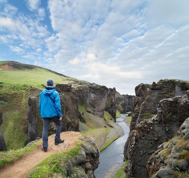 Turista em pé no topo do canyon na islândia