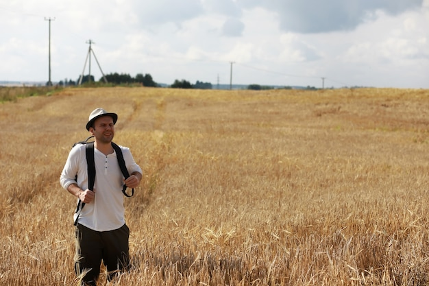 Turista em um campo de plantas de cereais. um homem em um campo de trigo. colheita de grãos.
