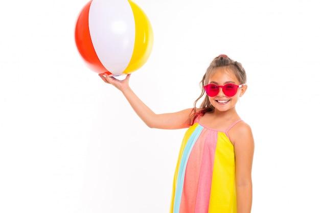 Turista em um vestido listrado segura uma bola listrada colorida para nadar em branco