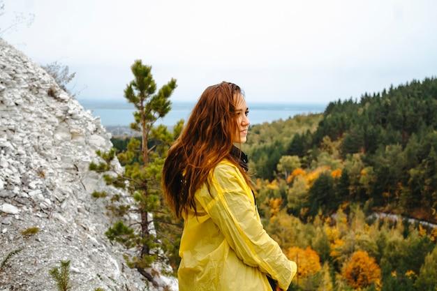 Turista em uma capa de chuva amarela