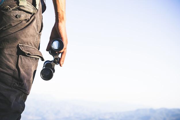 Turista está segurando através de binóculos no céu nublado ensolarado do topo da montanha.