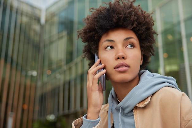 Turista étnica da moda com cabelo encaracolado usa smartphone para ligar e faz conversa internacional por celular por meio de aplicativo vestido com capuz desviando o olhar poses em edifício de vidro da cidade