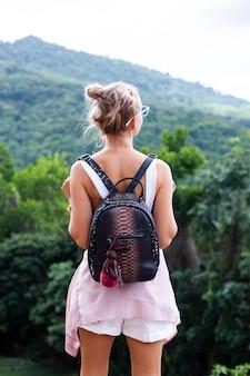 Turista europeia elegante mulher fica no topo de uma montanha com vista tropical incrível da ilha de koh samui. tailândia moda retrato ao ar livre de mulher