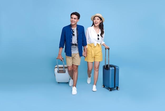Turista feliz casal asiático com bagagem, desfrutando de sua escapadela de férias de verão juntos, isolados sobre fundo azul.