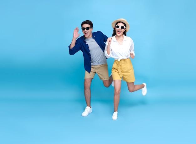 Turista feliz casal asiático energético correndo para viajar nos feriados isolados sobre fundo azul.