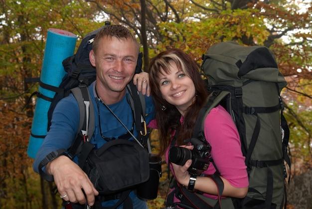 Turista feliz casal homem e mulher na floresta de outono com mochilas