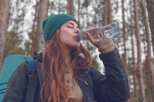 Turista feliz da mulher com água potável da trouxa da garrafa na natureza.