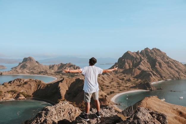 Turista feliz em pé no topo de uma montanha rochosa enquanto aprecia a vista do mar