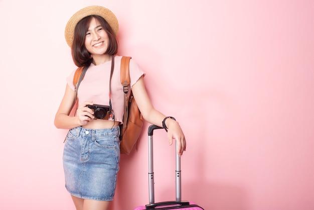 Turista feliz mulher asiática na parede rosa