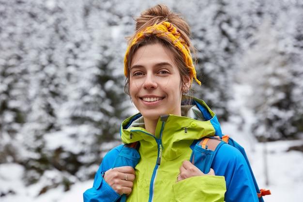Turista feliz posa no topo de uma montanha com neve, gosta de caminhadas no dia de inverno, usa uma faixa amarela na cabeça e jaqueta casual