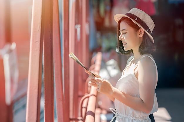 Turista fêmea novo que olha o mapa em sua mão ao viajar.
