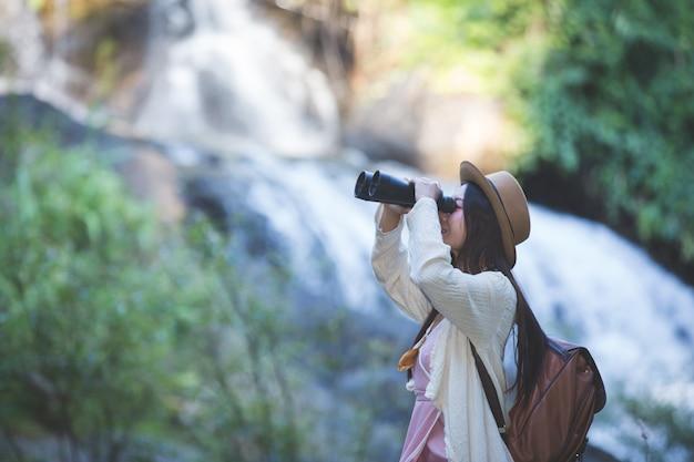 Turista fêmea que está olhando os binóculos para ver a atmosfera na cachoeira