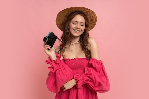 Turista feminina cabeça muito vermelha com câmera. mulher espantada segurando uma câmera retro azul e posando em rosa