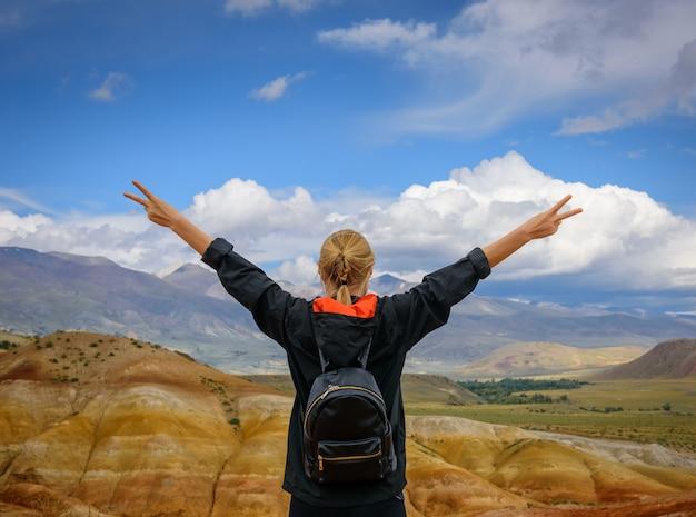 Turista feminina em pé de costas para a câmera, segurando as mãos contra a deslumbrante paisagem montanhosa num dia ensolarado de verão.
