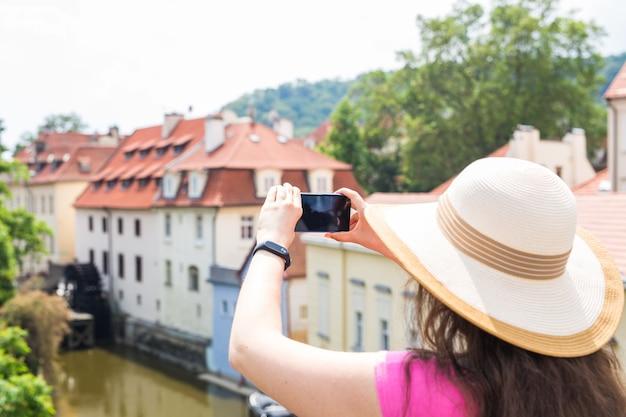 Turista feminina tirando uma foto com o telefone celular.